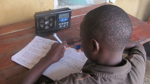 In Freetown, 11-year-old Joseph Sheriff of YMCA Primary school Freetown listens to radio lessons, and takes down notes as part of a program to educate the young as the schools are shut down due to Ebola.