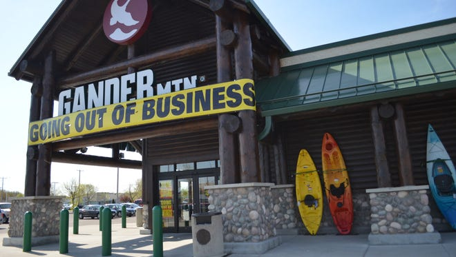 "A ""going out of business"" banner is displayed above the front entrance doors of Gander Mountain, Waite Park."