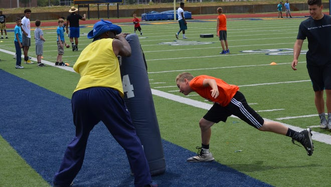 Battle Creek Central is hosting the Junior Bearcat Football Camp for grades 3rd-6th this week at C.W. Post Field. Above, camp coach Marc Casselle works with a young player on a tackling drill.