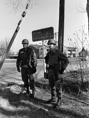 In this March 20, 1965 file photo, National Guardsmen, called to active federal duty by President Lyndon B. Johnson to protect marchers planning to march from Selma, Ala., to the state capitol at Montgomery, stand under a road sign showing the distance to the capital. The demonstration ended at the capitol building in a rally protesting voting regulations in Alabama.