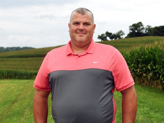 Matt Bell stands near a cornfield on his family farm in Zanesville, where they raise hogs, corn, soybean and wheat. Matt expects to receive a subsidy but said farmers would be better served by trade agreements.