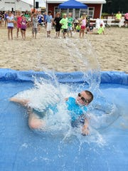 Mason Hay, 9 of Harrington, splashes into the water hazard during the obstacle team competition at fun and games on the last day of the Delaware State Fair.