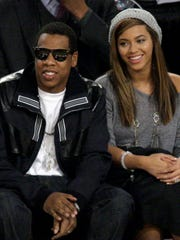 Music superstars and husband-and-wife  Jay-Z, left, and Beyoncé, right, shown watching the NBA All-Star basketball game in Feb. 2009.