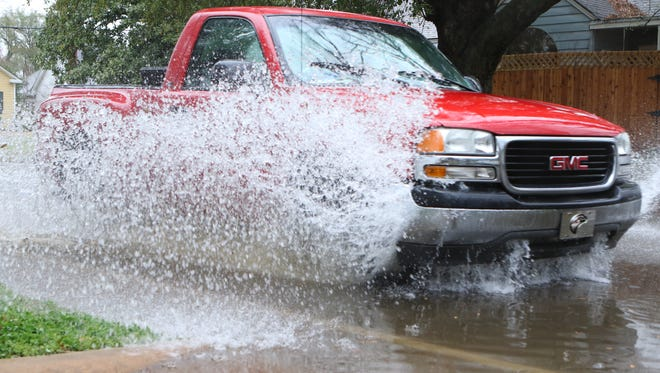 A truck drives through a flooded area near the intersection of Fifth Street and Hilton Street in Monroe on Wednesday.