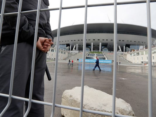 A security man stands guard at the soccer stadium on Krestovsky Island which will host some 2018 World Cup matches, under construction in St.Petersburg, Russia, Saturday, Sept. 10, 2016. Delegation from FIFA and the 2018 FIFA World Cup Russia Local Organising Committee (LOC) are making an operational planning tour of the Russian stadiums which will host 2018 FIFA World Cup. (AP Photo/Dmitri Lovetsky)