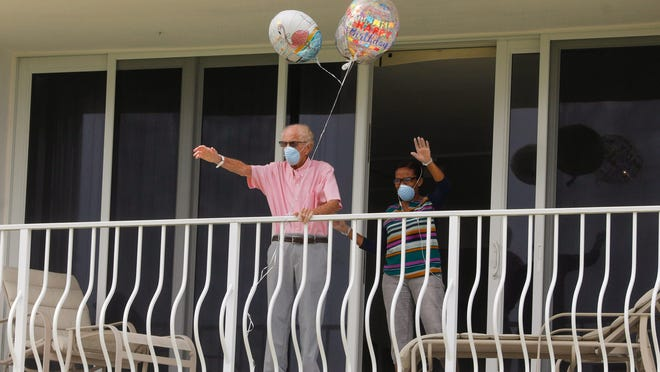 World War II veteran Matthew Allen waves to friends April 10 from balcony s they wish him a happy 100th birthday from below at his condominium complex.