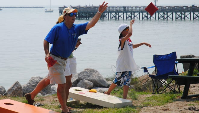 People compete in a bean bag toss game at Cape Charles Beach as part of the town's July 4 celebration on Sunday, July 3, 2011.