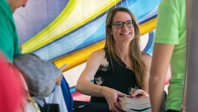 Author Sara Shepard chats with a fan while signing books at the Southwest Florida Reading Festival on Saturday at Centennial Park in Fort Myers.