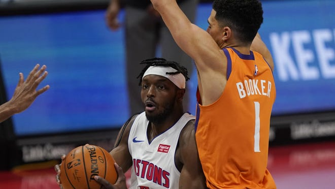 Detroit Pistons forward Jerami Grant drives on Phoenix Suns guard Devin Booker (1) during overtime of of an NBA basketball game, Friday, Jan. 8, 2021, in Detroit.