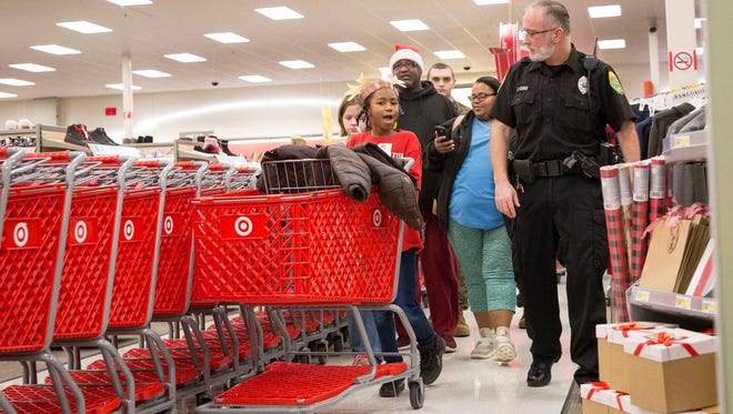 Officers from several police departments across Delaware County walk and shop with children during the annual Heroes and Helpers event on Dec. 16 at Target. The annual event helps get Christmas gifts for children for families in need.
