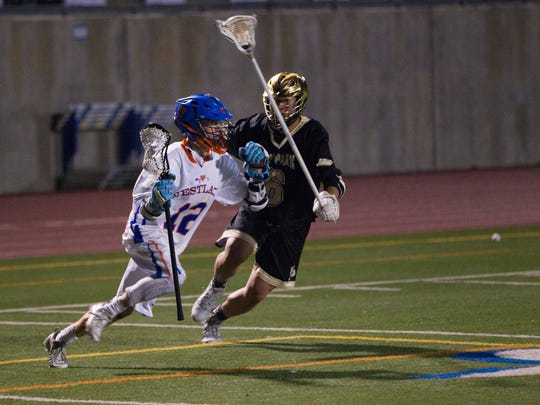 Westlake High attackman Nick Reilly takes on Oak Park defender Alastair Ong during a non-league boys lacrosse match on Feb. 28. Westlake won, 14-9.