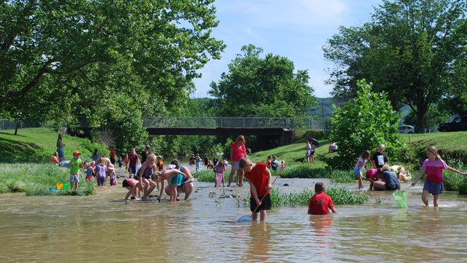 People in Banklick Creek at Pioneer Park, 3951 Madison Pike, Covington.
