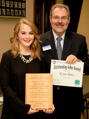 District 4-H Educator, Michael Martin, presents the Outstanding 4-H'er Award to Kyra Rotz, Greencastle.