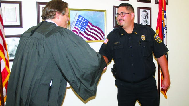 Booneville Police Chief Ben Villarreal (right) shakes hands with District Judge Brian Mueller after a swearing in ceremony for Villarreal last week.