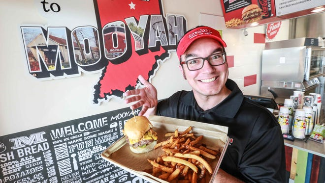 Franchise owner Chris Frank holds up a burger and fries at Mooyah, a new family friendly burger joint at 17147 Mercantile Blvd., Noblesville, on Sept. 8, 2015.