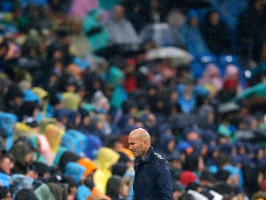 Real Madrid's head coach Zinedine Zidane walks back to the bench during a Spanish La Liga soccer match between Real Madrid and Villarreal at the Santiago Bernabeu stadium in Madrid, Spain, Saturday, Jan. 13, 2018. (AP Photo/Paul White)