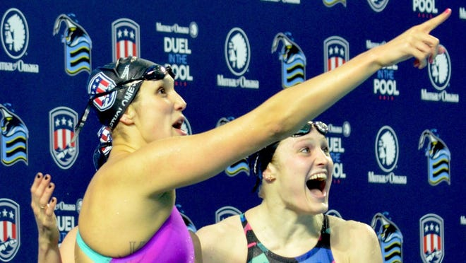 """Courtney Bartholomew (left) and Kelsi Dahlia celebrate after looking up at the scoreboard and seeing """"WR"""" by their time in the 400 medley relay at the 2015 Duel in the Pool in Indianapolis."""