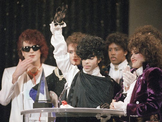 """In this Jan. 28, 1985, file photo, pop vocalist Prince holds up a hand as he and his band The Revolution accept the American Music Award for best single """"When Doves Cry"""" in Los Angeles. The Revolution is preparing to kick off a spring U.S. tour with a performance Friday, April 21, 2017, at Paisley Park in the Minneapolis suburb of Chanhassen, on the first anniversary of the Prince's death from an accidental painkiller overdose."""