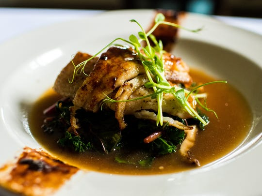 The Miso Gulf Fish, plated with a fish sauce caramel, mushrooms, garlic ginger greens, and a lemongrass broth, is served at the Saint Street Inn in Lafayette, La., Saturday, Oct. 31, 2015.