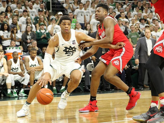 Michigan State guard Miles Bridges (22) drives the baseline against Ohio State forward Jae'Sean Tate (1) during the second half of MSU's 74-66 win Tuesday at Breslin Center.