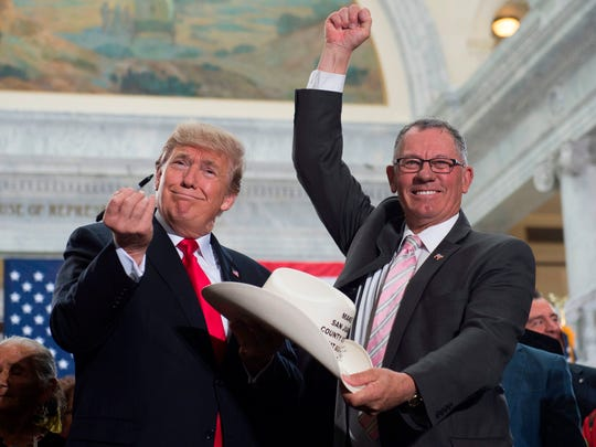 US President Donald Trump holds up a pen after signing