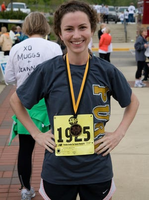 """In this 2012 photo, Lisa Strueh wears the first place medal for her age class after finishing """"The Challenge 5K Run/Walk""""  at Purdue."""