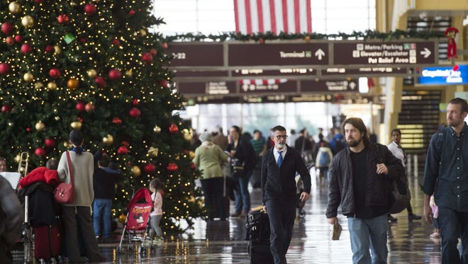 Passengers head to their flights at Reagan National Airport in Arlington, Va.
