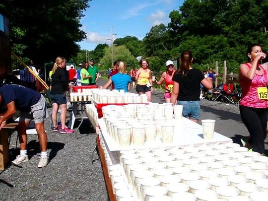 A table of water-filled paper cups at the Highland water station allows runners to grab a cup and go during last year's Walkway Marathon.