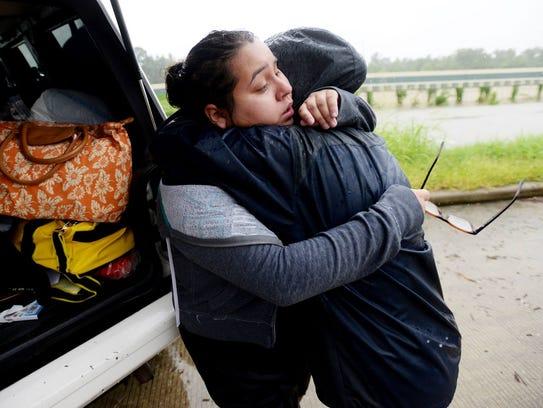 MJ Torres gives her sister, Valere Garza, left, a hug