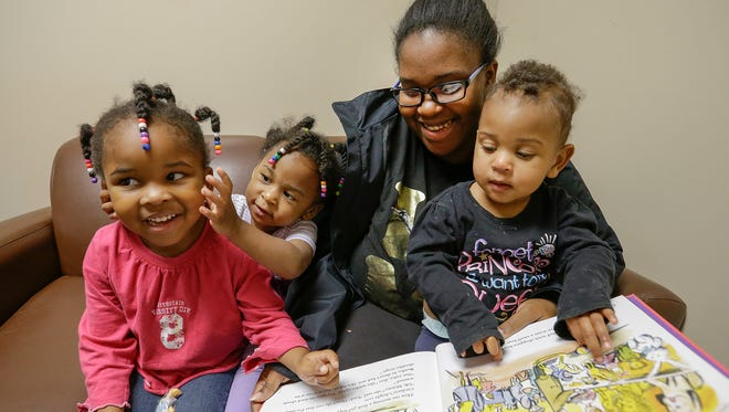Adrienne Brown and her three daughters, Leilah,4, Grace,2, and Olivia,1, been staying at Wheeler Center for Women and Children since July. This is the family in their private room Monday, Nov 13, 2017.