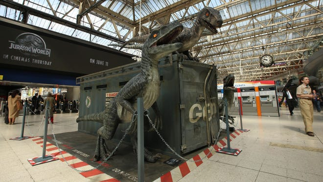 Commuters walk past the model Raptors as part of the Jurassic World Waterloo station exhibition in central London on June 8. Rebecca McKean of St. Norbert College says Hollywood ignored science when it depicted these raptors as having scales as opposed to feathers.