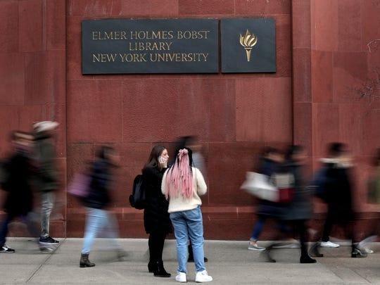 Two students pause while walking along Washington Square