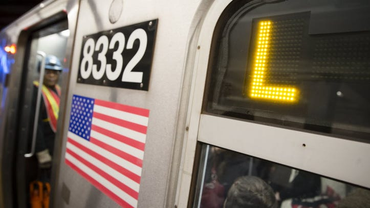 Riders stand inside an L-Train subway car, on Oct.
