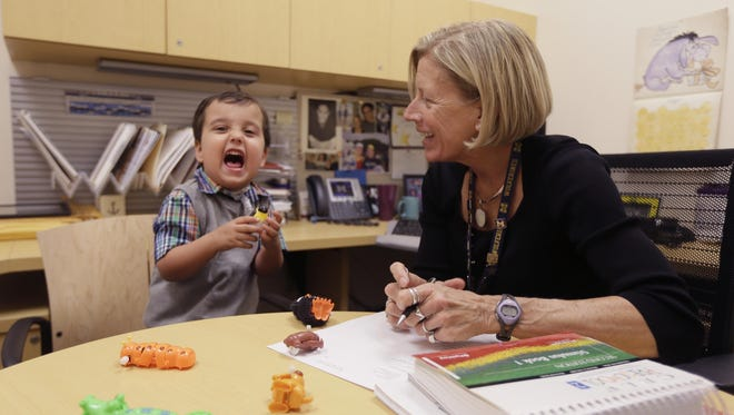 In a photo from Oct. 22 in Ann Arbor, Mich., Grant Hasse yells out a word next to Lynn Driver, a speech-language pathologist at the University of Michigan's C.S. Mott Children's Hospital.