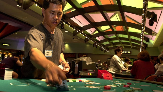Francis Roblete a dealer at the new Augustine Casino in Coachella in 2002 practices and refines his dealing skills on Monday before the casino has opened. Augustine Casino will undergo a complete renovation in the coming weeks.