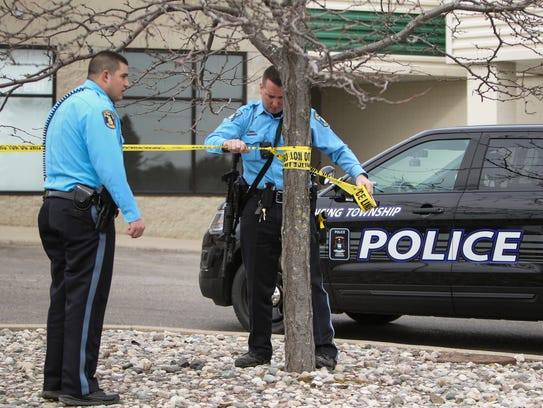 Members of the Lansing Police Department tape off an