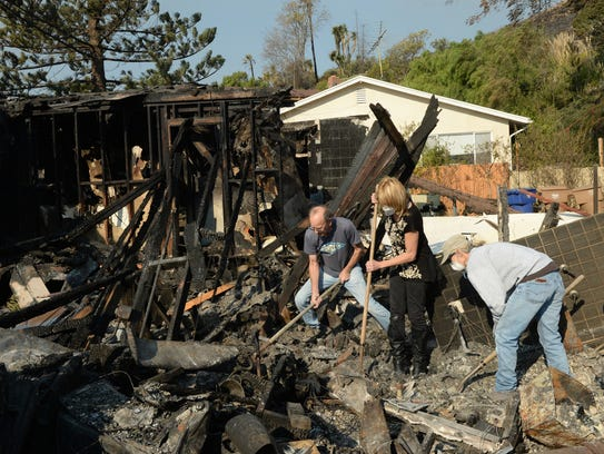 Ventura homeowner Adele Bonge, center, is assisted