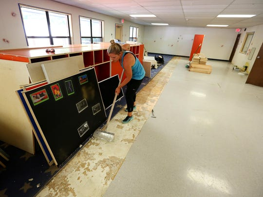 Julia Haney prepares the floors for new carpet at the new Montessori Discovery Academy at 875 Promontory Place SE, Wednesday, August 12, 2015, in Salem, Ore.