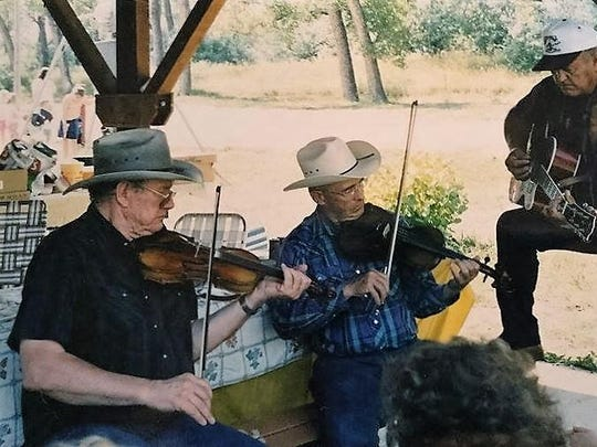 Frank Crowder, left, plays the fiddle at his family