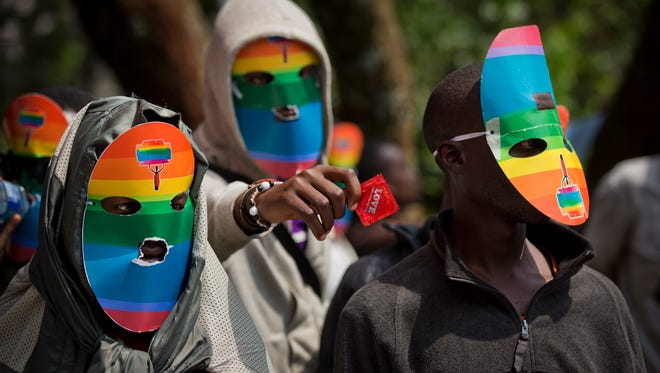Kenyan gays and lesbians and others supporting their cause wear masks to preserve their anonymity and one holds out a wrapped condom, as they stage a rare protest, against Uganda's increasingly tough stance against homosexuality in 2014.