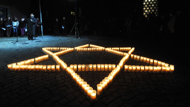Rabbi Shneur Trebnik holds a speech next to  a Star of David made of candles at  the synagogue in Ulm, Germany on Saturday.