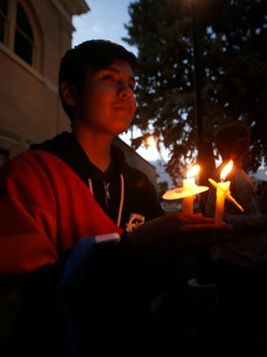 Rakeen Tahe holds a candle on Monday at Orchard Park in Farmington during a vigil to remember the victims of a mass shooting at a nightclub in Orlando, Fla.