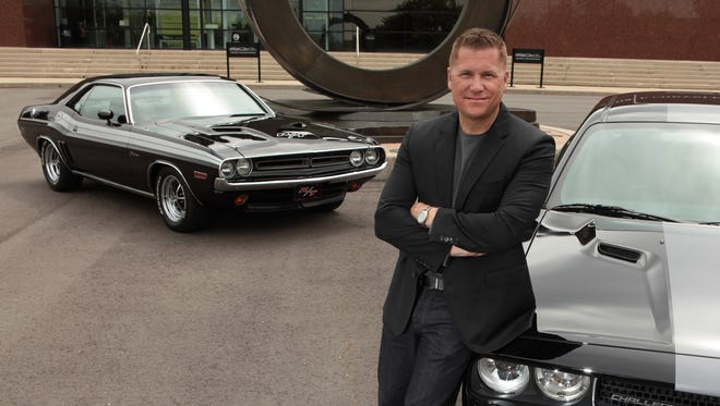 File photo of Timothy Kuniskis, CEO of Fiat Chrysler's Dodge brand, with his personal 1971 Dodge Challenger, left, and a current version, right.