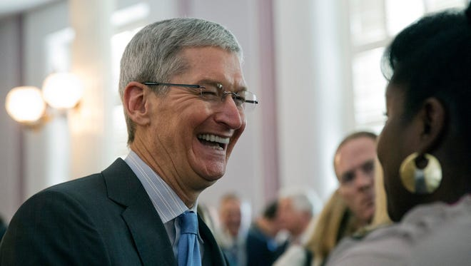 Apple chief executive and Alabama native Tim Cook laughs with a group before an Alabama Academy of Honor ceremony at the state Capitol in this Oct. 27, 2014 file photo taken in Montgomery, Ala.