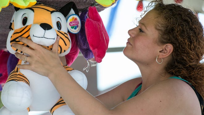 Jessica Carnucci hangs a stuffed toy prize at a game stand on Thursday, June 1, 2017.