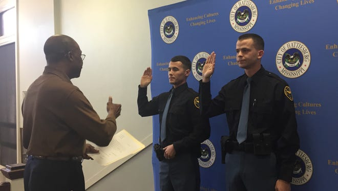 Mayor Johnny DuPree administers the oath of office to two new Hattiesburg police patrolmen, Christopher McDonald, left, and Thomas Reid.