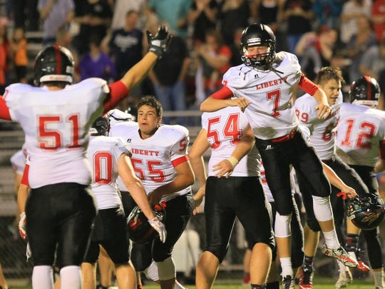 Liberty's Austin Kemp (7) and teammates celebrate a