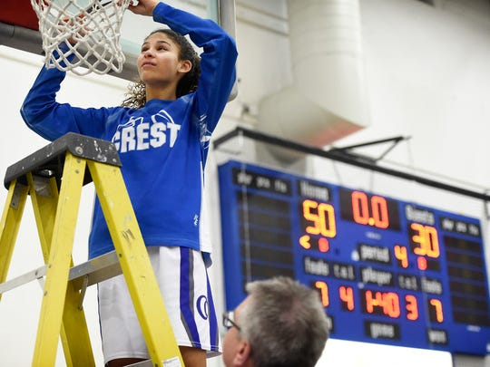 Cedar Crest guard Ariel Jones cuts down a piece of the net after the Falcons clinched their second straight Section 1 title on Friday night.