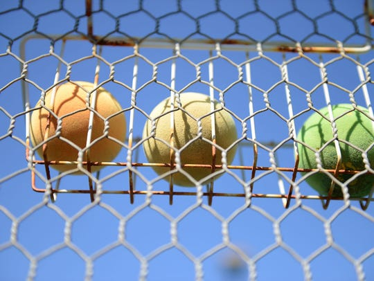 Extra platform tennis balls stored on the court fence