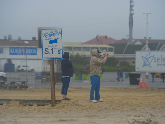 People take photos of the rough surf in Ocean City,